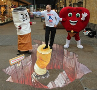 Peter Hollins stands with No Smoking Day mascots above a picture of a cigarette being stubbed out